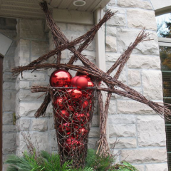 This outdoor planter with large stars made of branches and bright red Chistmas ornaments creates a wow statement