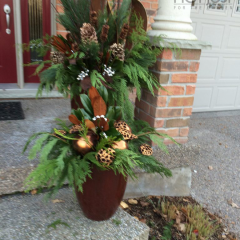 Porch pots with evergreen branches and gold and bronze accents are perfect for fall and winter