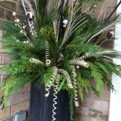 Large decorative front door Christmas planter with evergreens mixed with gold decorative accents to add texture