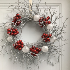 Unique Christmas wreath made of silver branches with an added pop of red and white ornaments
