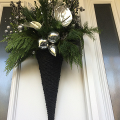 Cone-shaped winter door arrangement with champagne accents and evergreen branches transforms basic doors