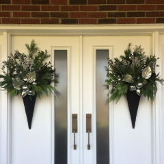 Matching Christmas door arrangements with evergreen branches and champagne accents elevate the front entryway