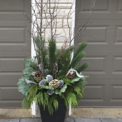 Large winter outdoor planter adorned with evergreen branches and large frosted pine cones