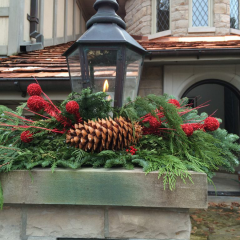 Decorative Christmas foliage with a large pine cone and bright accents